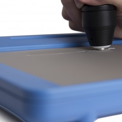 An inTACT Eraser is erasing a raised line on a blue inTACT sketchpad